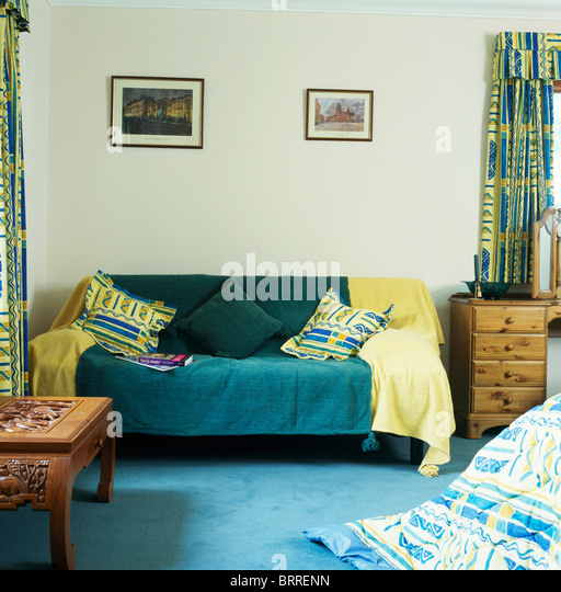 Yellow And Dark Green Throws On Sofa In Economy Style Bedroom With Blue  Carpet