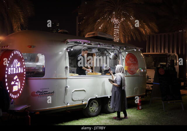 A Lady In Head Cover Looking At The Smartphone Mia Strada Airstream Food Stand