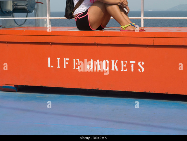 Attractive Girl Sitting On Life Jackets Storage Onboard A Cruise Ferry   Stock Image