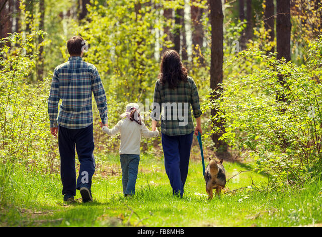 Family With Dog Walking In The Forest Back To Camera