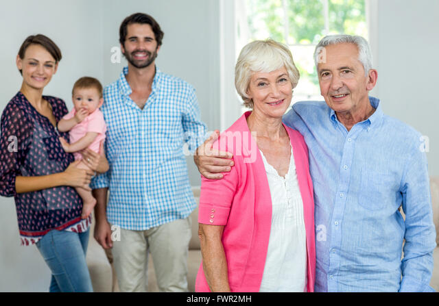 Young Couple And Senior Couple Standing In Living Room Stock Photos ...