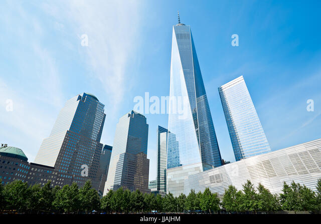one world trade center skyscraper surrounded by glass buildings and green trees blue sky in