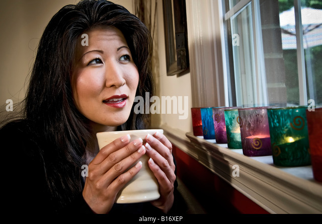 an asian woman holds a large cup of tea while looking out a window