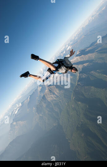 A skydiver tracking above Locarno, Switzerland with the Alps in the background - Stock Image