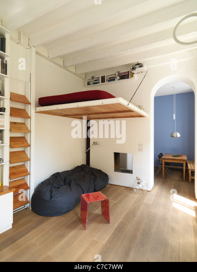 suspended bed above the sofa in modern apartment with wood floor stock image