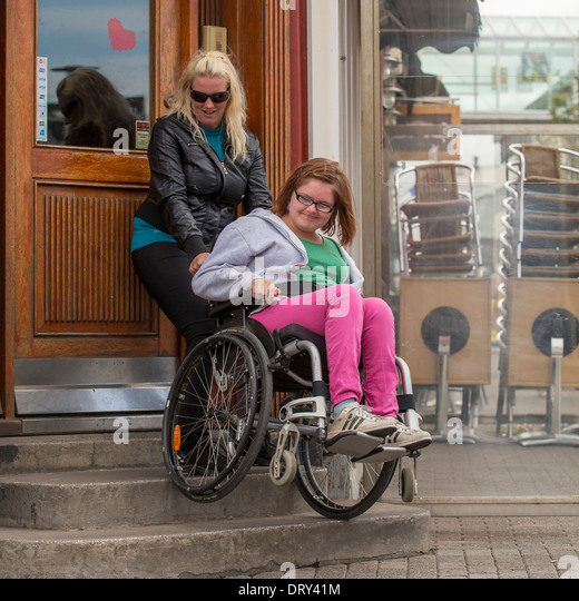 caregiver-helping-disabled-girl-in-wheelchair-up-the-steps-reykjavik-dry41m.jpg