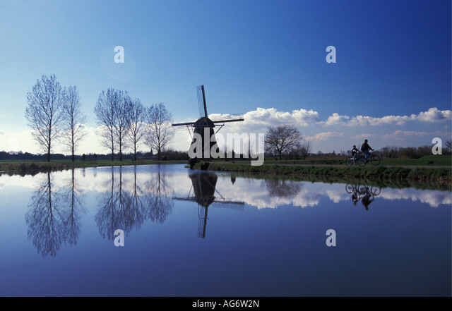 Abcoude Netherlands  City pictures : Netherlands Abcoude Family cycling by Gein River with windmill Stock ...