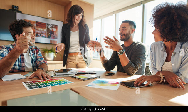 Young and creative start-up team discussing ideas in board room. Group of multi ethnic people during business meeting. - Stock Image