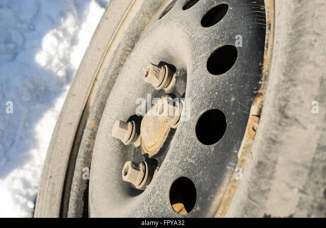 closeup of car wheel with a removed hubcap the tyres are worn with snow on