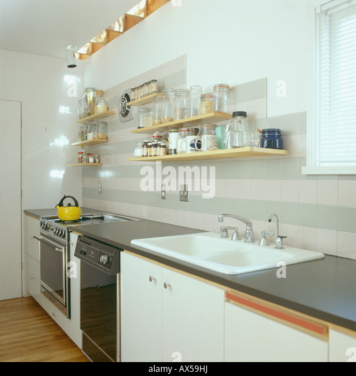 Medium image of shelves above double white sink in modern white galley kitchen   stock image