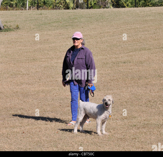 Woman With Her Standard Poodle At The Bicentennial Park Dog In Ormand Beach Florida