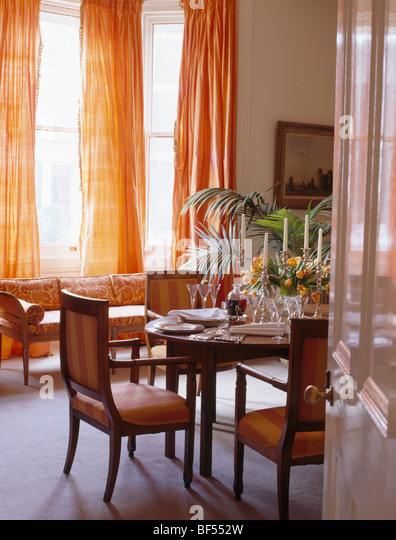 Door Open To Traditional Townhouse Dining Room With Orange Silk Curtains And 18th Century Furniture