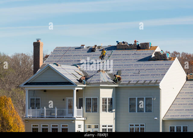 Workmen On Roof Of An American Home Replacing Roofing Felt Ready To Replace  Tiles On The