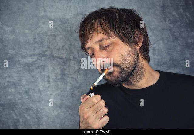 Portrait of casual adult man lighting up cigarette - Stock Image  sc 1 st  Alamy & Man Lighting Up Cigarette Stock Photos u0026 Man Lighting Up Cigarette ... azcodes.com