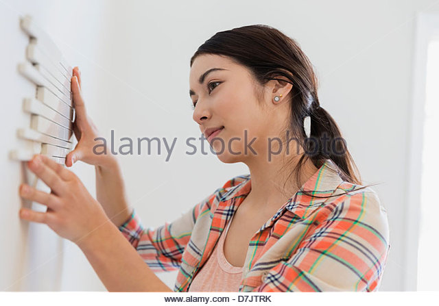 young woman decorating wall with tiles at home stock image