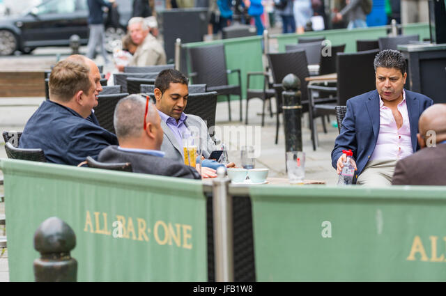 Smart middle aged men in suits sitting outside at a bar in Brighton. - Stock Image