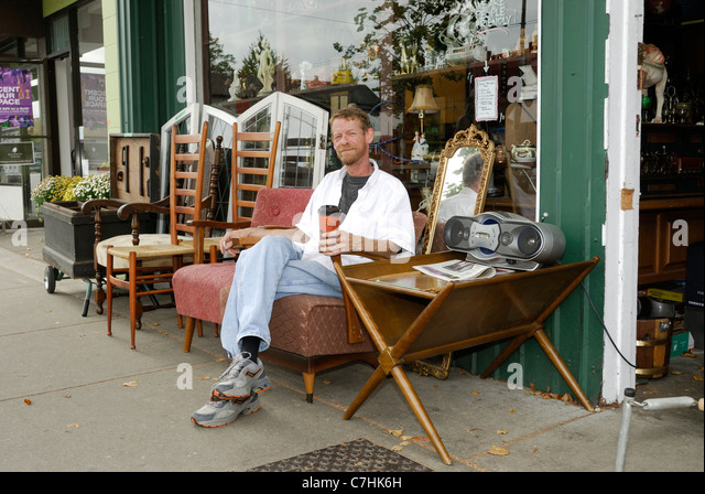 Used furniture shopkeeper sitting outside on a piece of furniture.Used and antique  furniture stores - Antique Piece Of Furniture Stock Photos & Antique Piece Of