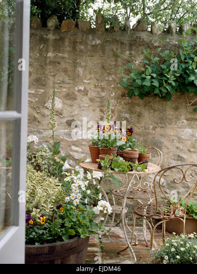 French Doors Open To Small Cottage Patio With Pansies And White Daisies  Growing In Pots