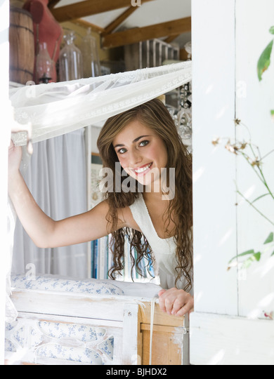 woman opening a window in a quaint house and looking out stock image