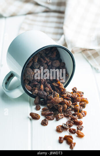 Sweet dried raisins in cup. - Stock Image