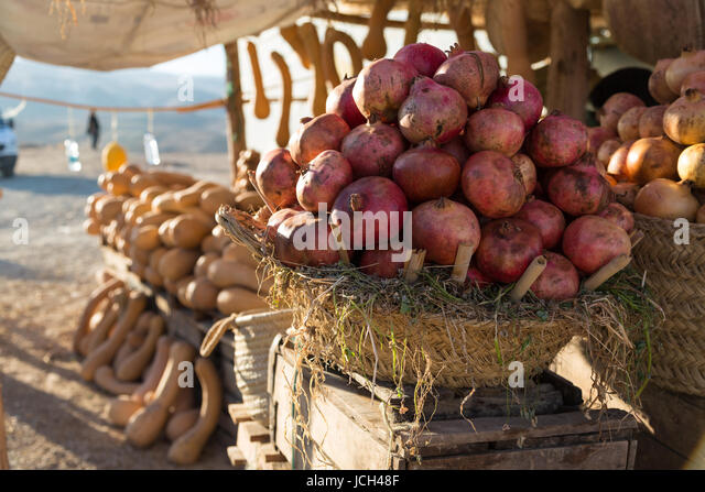 A roadside stop above a reservoir near Meknes in Morocco is piled with pomegranates and orange suash in many different - Stock Image