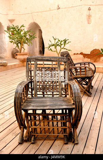 wicker armchair with old wall background on patio in mexican style stock image