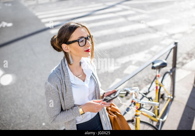 Businesswoman outdoors with bicycle - Stock Image