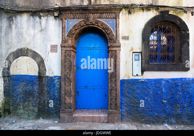 Windows and doorways of different shapes and colours on every house in the old town of Essaouira, Morocco - Stock Image