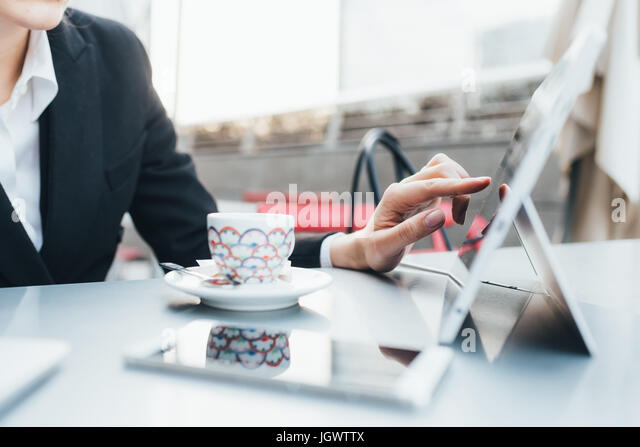Businesswoman using digital tablet in coffee shop - Stock Image