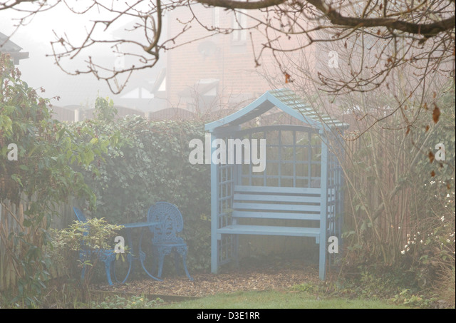 blue garden furniture in garden corner on mister winters day stock image