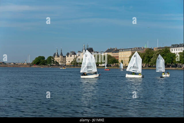 Junior sailors in optimist dinghies on the Peblinge Lake in central Copenhagen. View towards Søtorvet and Dronning - Stock Image