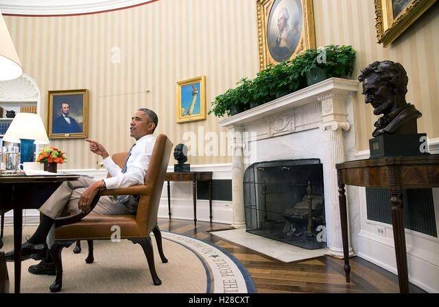 oval office fireplace. U.S. President Barack Obama Sits At His Desk During A Meeting In The White House Oval Office Fireplace