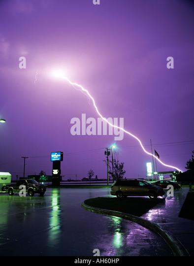 lightning strikes over a wet car park and motel sign in valentine nebraska stock image
