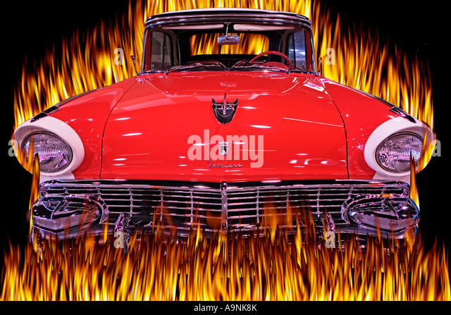 front end view of a fully restored ford fairlane exploding through a wall of flames