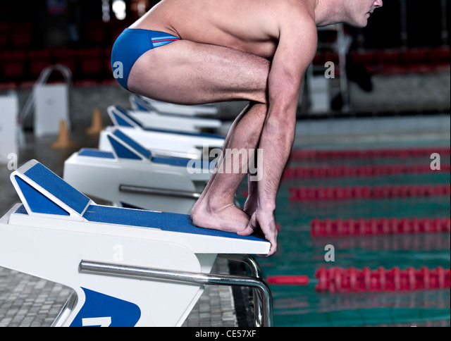 swimmer on starting blocks at pool edge stock image