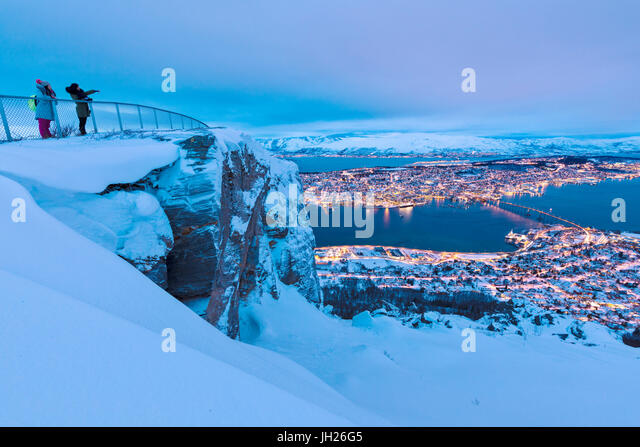 People admire the city of Tromso at dusk from the mountain top reached by the Fjellheisen cable car, Troms, Northern - Stock Image