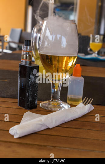 Vaporizer and smoking beer with bottle and fork on table - Stock Image