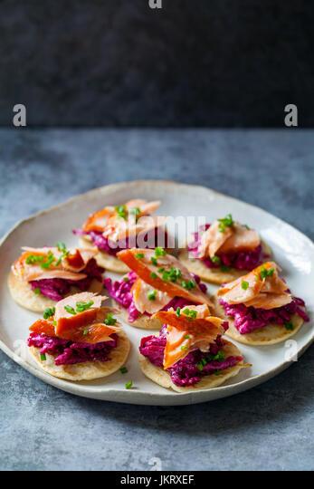 Blinis with beetroot, horseradish, hot smoked salmon and goat chhese - Stock Image