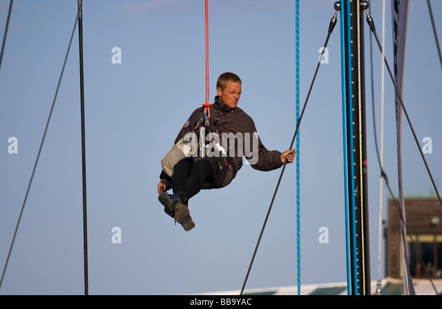 crew member hanging from mast on a bosunu0027s chair