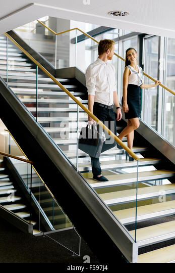office stairs. businessman and businesswoman walking taking stairs in a modern office building stock image s