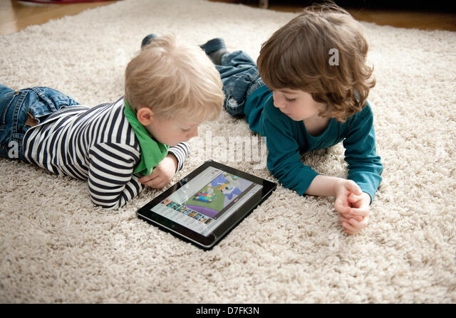 Two Little Boys Are Lying On The Floor Watching An Animated Cartoon Ipad
