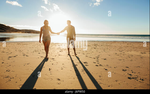 Outdoor shot of romantic young couple walking along the sea shore holding hands. Young man and woman walking on - Stock Image