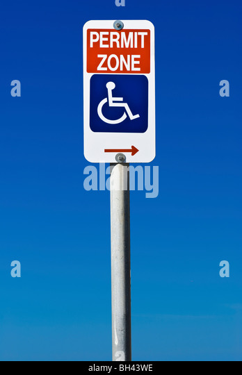 a sign indicating disabled permit parking only isolated on a blue bh43we - miami beach wedding permit