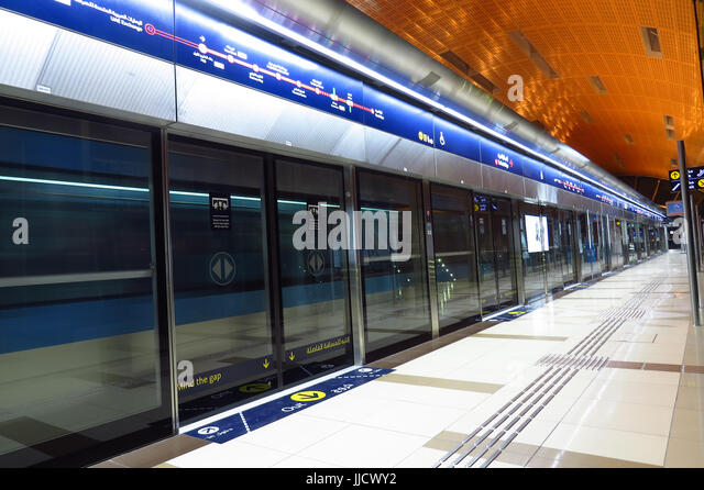 A metro train speeding past a metro station in Dubai, United Arab Emirates - Stock Image