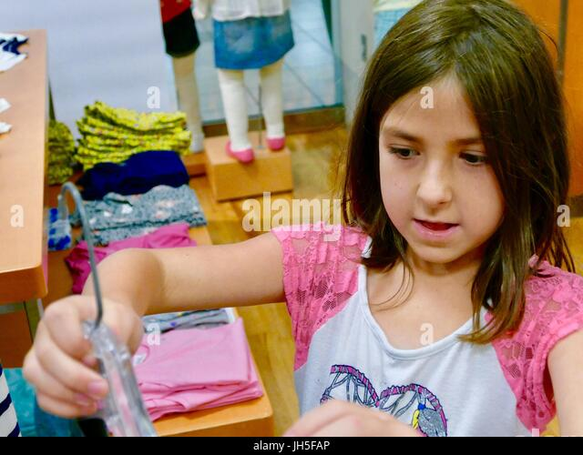 Little girl shopping in the children's department of a retail clothing store in Florida, USA. - Stock Image