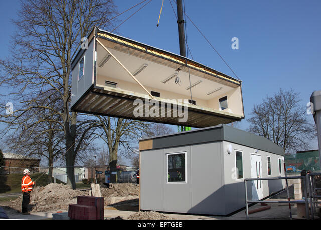 A section of a modular building hangs from a crane during the installation  of a new