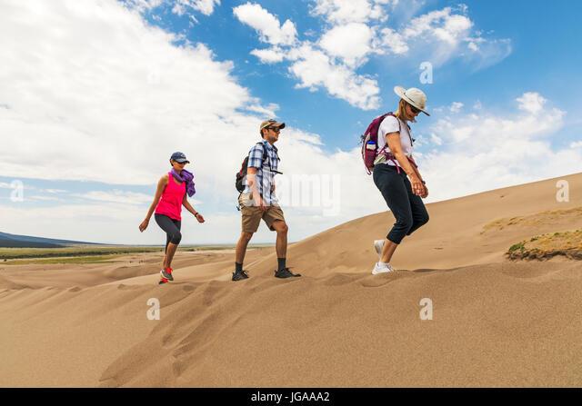 Visitors explore the Great Sand Dunes National Park & Preserve; San Luis Valley; Colorado; USA; 44,246 acres - Stock Image