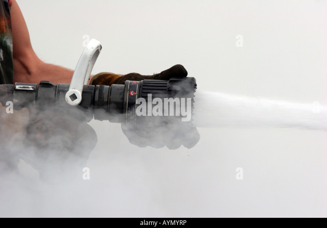 A-sexy-firefighter-holding-the-nozzle-of-a-hoseline-spraying-water-AYMYRP.jpg