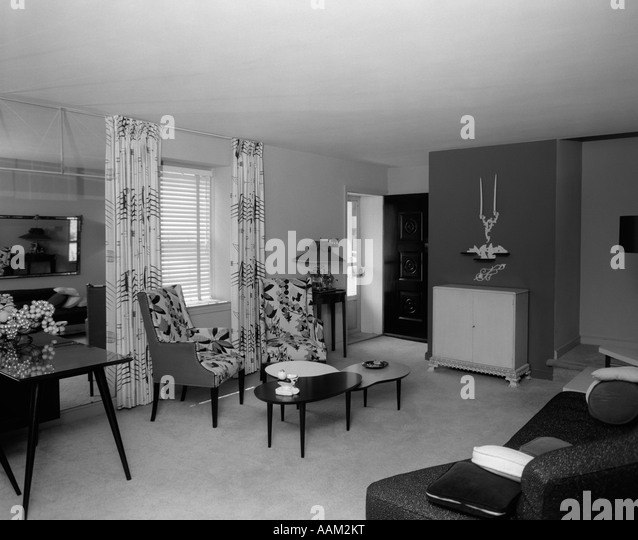 1950s LIVING ROOM INTERIOR WITH KIDNEY SHAPED COFFEE TABLES FLOOR LENGTH CURTAINS VENETIAN