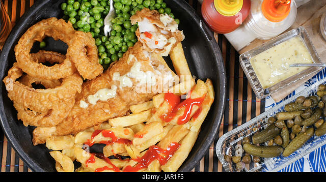 Top down view of an English fish and chips with garden peas, ring onions and tartar sauce - Stock Image